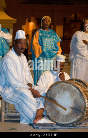 Vertical close up of traditional Moroccan singers and musicians playing the 'bendir' drum at night. - Stock Photo