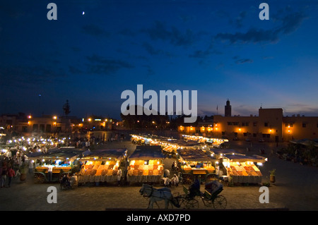 Horizontal elevated cityscape of Place Jemaa El Fna or Jemaa el-Fnaa or Jamaa al-fanâ lit up at night with a horse - Stock Photo
