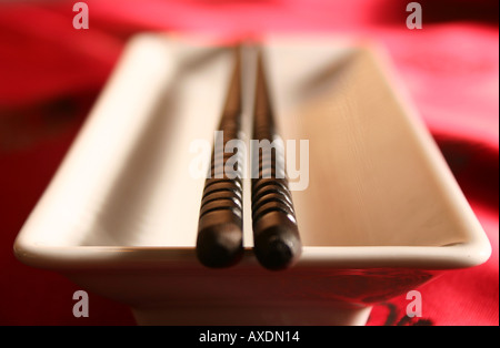 Chopsticks on a bowl in a formal dinner setting - Stock Photo