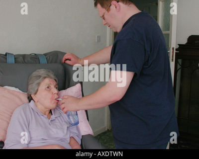male carer giving an elderly woman with multiple sclerosis a drink of water with a straw - Stock Photo