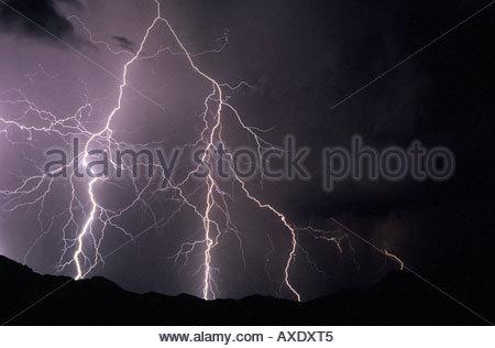 Big  lightning bolts on left side of image striking distant Catalina Mountain Range. - Stock Photo