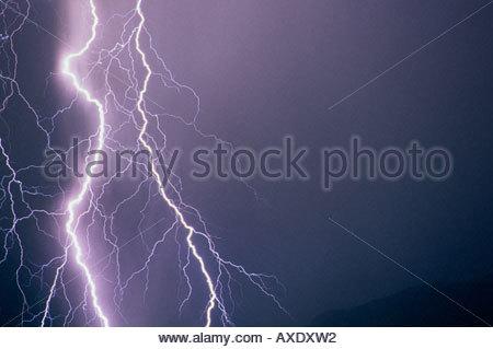 Big huge large lightning bolt on left side of image from a very close lightning strike. - Stock Photo