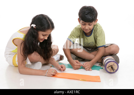 Boy and a girl tying string to a kite - Stock Photo