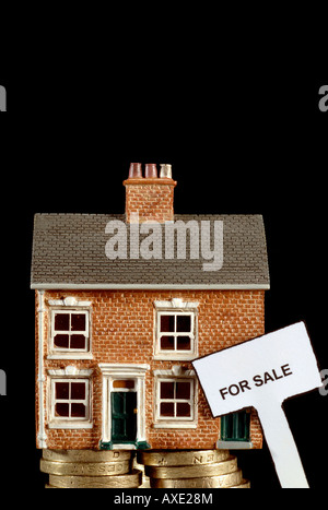 a house for sale sunk in debt balancing on a stack of british pound coins struggling under the recession - Stock Photo