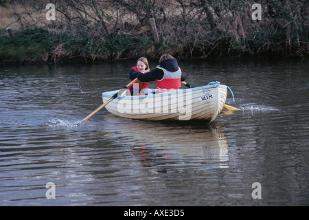 UK NORFOLK BROADS TWO GIRLS IN A ROWING BOAT WITH LIFE JACKETS WATER LAKES HOLIDAY LEISURE FUN SAFETY - Stock Photo
