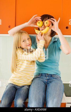Mother and daughter (8-9) in the kitchen, mother holding apples in front of her eyes, - Stock Photo