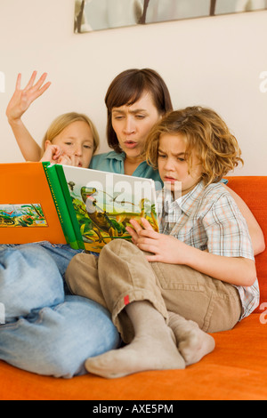 Mother reading story book to children - Stock Photo