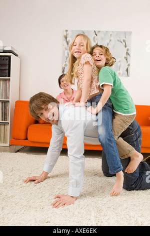 Boy (6-7) and girl (8-9) on father's back in living room - Stock Photo