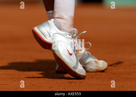 Close up of tennis players feet lifting off ther ground as he is serving. - Stock Photo