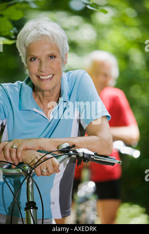 Senior woman with bike, man in the background - Stock Photo
