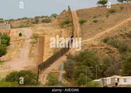 This is the existing border fence between the United States and Mexico near Nogalas, AZ and Nogalas, Sonora. - Stock Photo