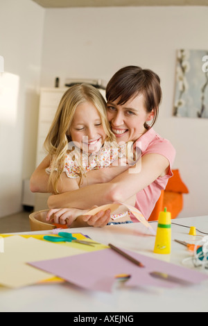 Mother embracing daughter (8-9), smiling, portrait - Stock Photo