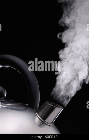 Steaming kettle Against a Black Background - Stock Photo