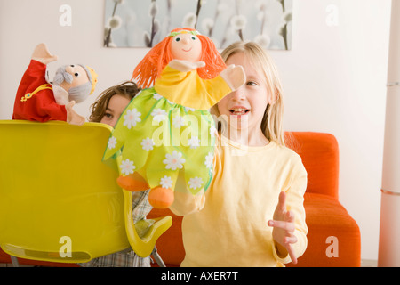 Girl (8-9) and boy (6-7) playing with glove puppets - Stock Photo