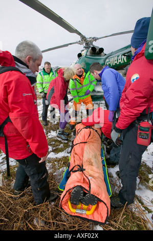 Members of Langdale Ambleside Mountain Rescue Team and an air ambulance doctor evacuate an injured walker - Stock Photo