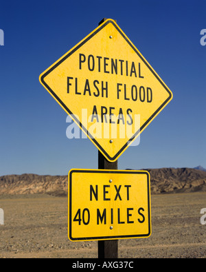 Yellow and black sign saying potential Flash Flood Areas Next 40 Miles in Death Valley National Monument California - Stock Photo