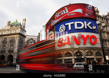 Picadilly Circus, London with bright billboards and red double decker bus blurred in foreground. - Stock Photo