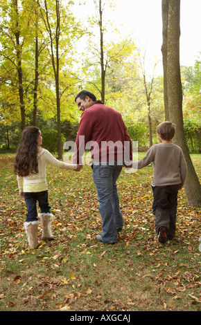 Father and Children Walking in Autumn - Stock Photo