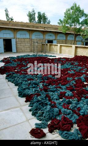 India Rajasthan crafts Barmer bundles of bundhini tie dyed cloth drying in yard - Stock Photo