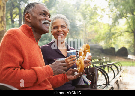 Couple with Coffee and Pretzels in City Park, New York City, New York, USA - Stock Photo