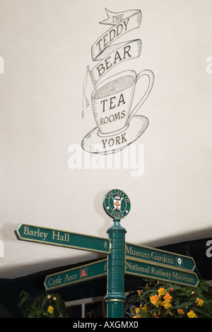 Tourist signpost by Teddy Bear Tearooms sign on wall in Stonegate in city centre York Yorkshire England UK - Stock Photo