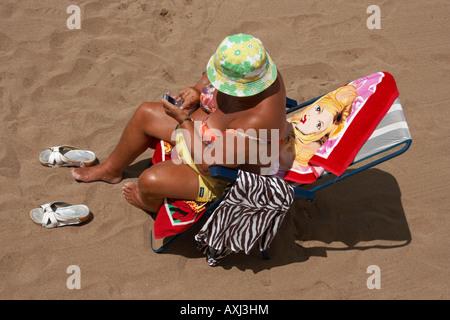 Mature Spanish woman using moblie phone on beach - Stock Photo