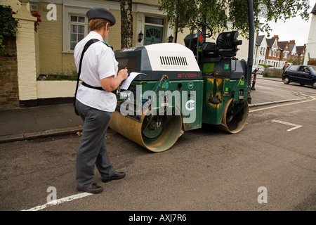 Traffic warden and road roller Twickenham Middlesex UK - Stock Photo