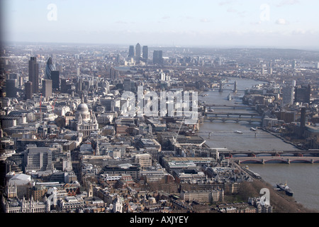 High level oblique aerial view south east of The City of London and Canary Wharf London EC4 EC3 EC2 England UK Feb - Stock Photo