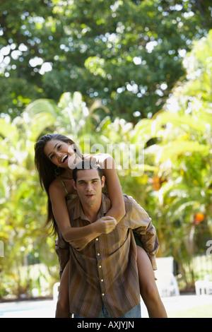 South American man giving girlfriend piggyback ride - Stock Photo