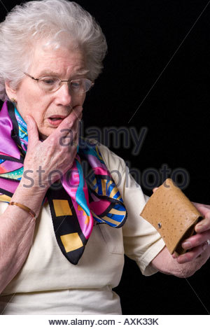 An old woman shocked to find her purse is empty. - Stock Photo