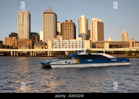 Central Business District buildings with City Cat ferry in evening summer sunlight with river Brisbane Queensland - Stock Photo