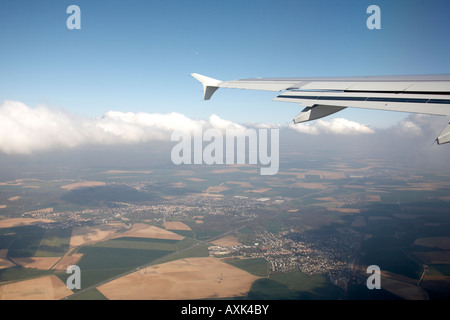 Aerial view of Frency countryside from the air with cumulus clouds and Airbus aircraft wing near Paris France Europe - Stock Photo