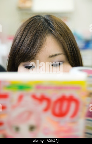 Young woman reading manga-style comic book, extreme close-up, cropped - Stock Photo