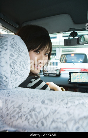 Young woman sitting in car, smiling over shoulder at camera - Stock Photo