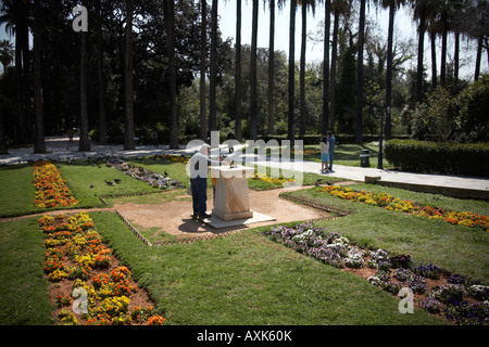 Flower beds with man at fountain in spring time in National Gardens Athens or Athini Greece - Stock Photo