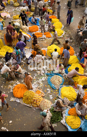 Buyers and sellers mill around in the colourful Mullick Ghat Flower Market near to the Howrah Bridge in Kolkata. - Stock Photo