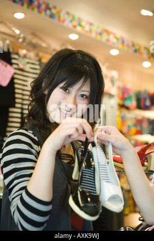 Young woman in shoe store holding two different colored shoes, smiling at camera - Stock Photo