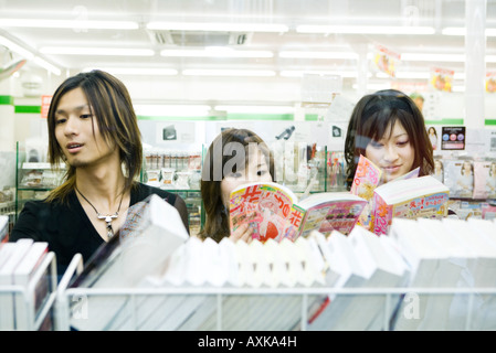 Three young friends side by side in store, looking at manga-style comic books - Stock Photo