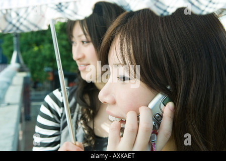 Two young women standing under parasol, one using cell phone, cropped view - Stock Photo