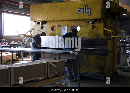 Stock photo of two factory workers operating a hydraulic CNC press brake machine - Stock Photo