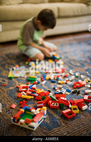 Boy aged six years plays with Lego building blocks - Stock Photo