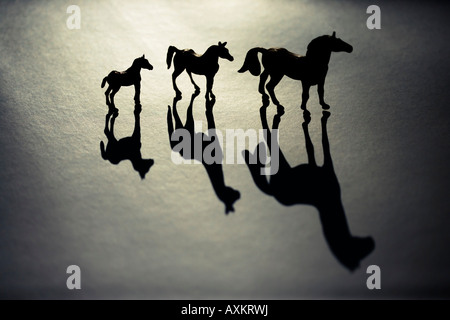 Toy horses in strong sunlight - Stock Photo