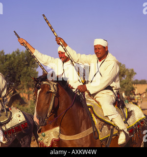Two Berber horsemen sitting on ornate silver filigree saddles in traditional long white robes & headbands Marrakech - Stock Photo