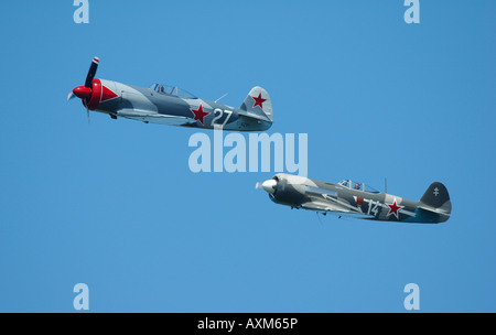 Two old Russian planes in formation flight: left Yak  3U and right Yak11, french vintage air show, La Ferte Alais, - Stock Photo