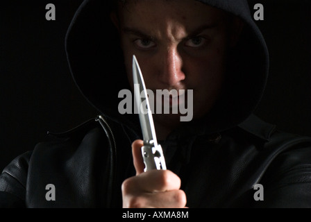 Teenage thug in hoody with knife - Stock Photo
