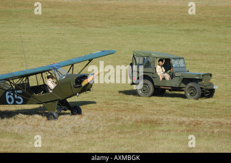 Old Piper J-3 Cub (L-4) plane anf famous Jepp car used during WWII in Europe by us army. - Stock Photo