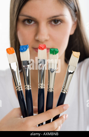 Paintbrushes with paint in front of woman s face - Stock Photo