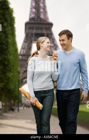 Couple walking with Eiffel Tower in background - Stock Photo