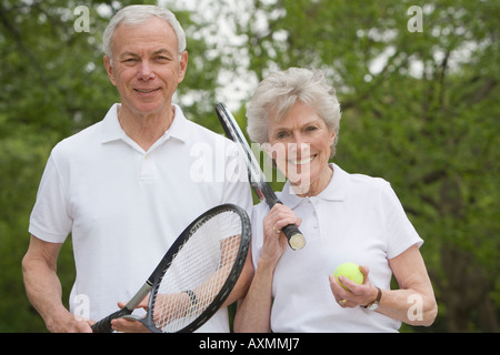 Portrait of mature couple with tennis racquets - Stock Photo