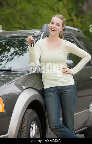 Young woman standing with her new car - Stock Photo